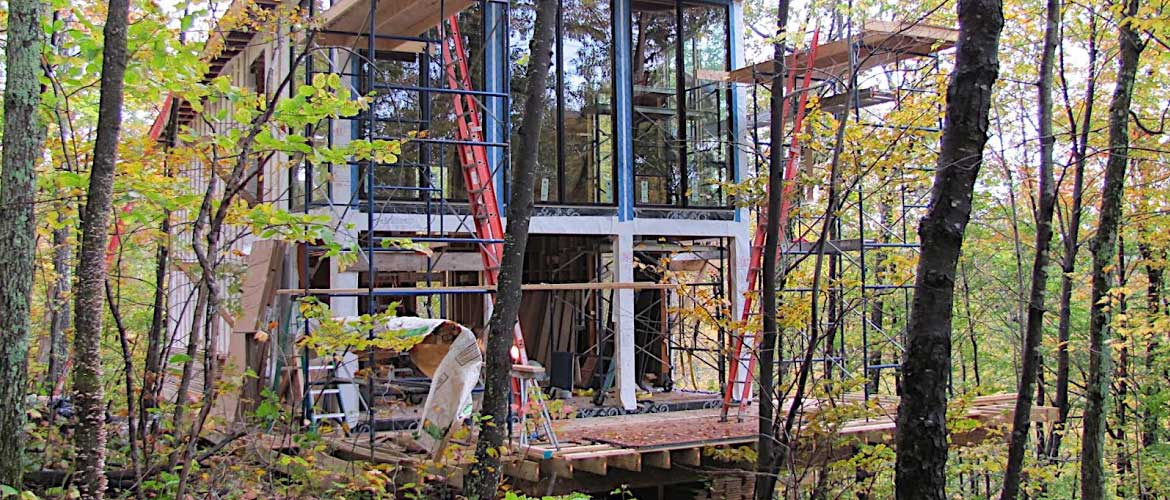 house in the trees by small building company construction site